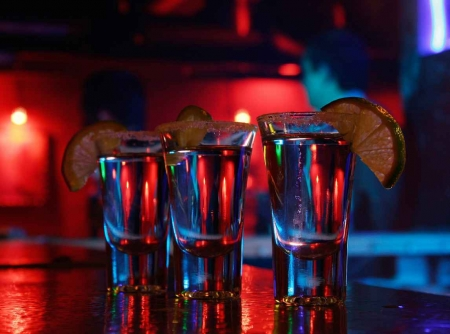 Three shots of tequila on a bar.