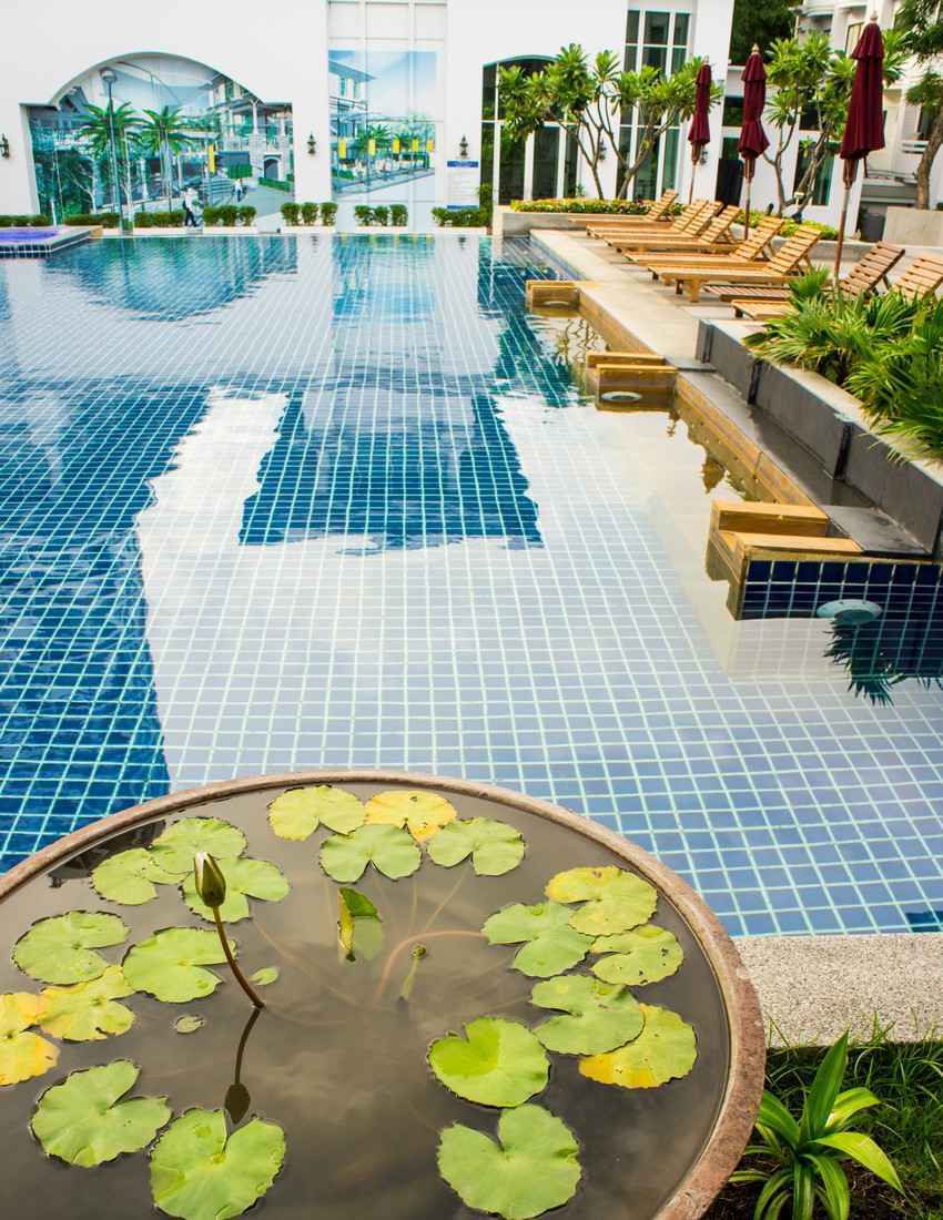 A large blue tiled swimming pool that is available for use by condo rental guests.