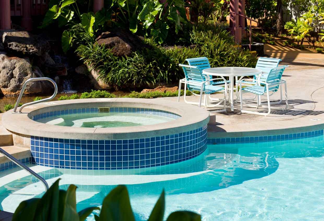 A Jacuzzi and a large swimming pool at a condo rental facility.