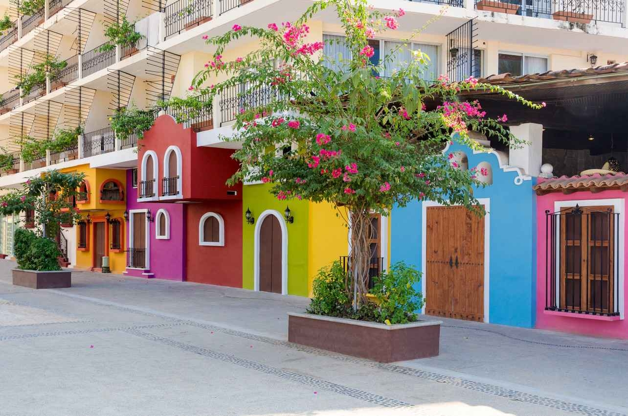 Several colorful condominiums near a Playa Del Carmen sidewalk and street.