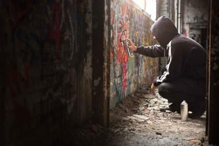 A man painting graffiti on a wall.