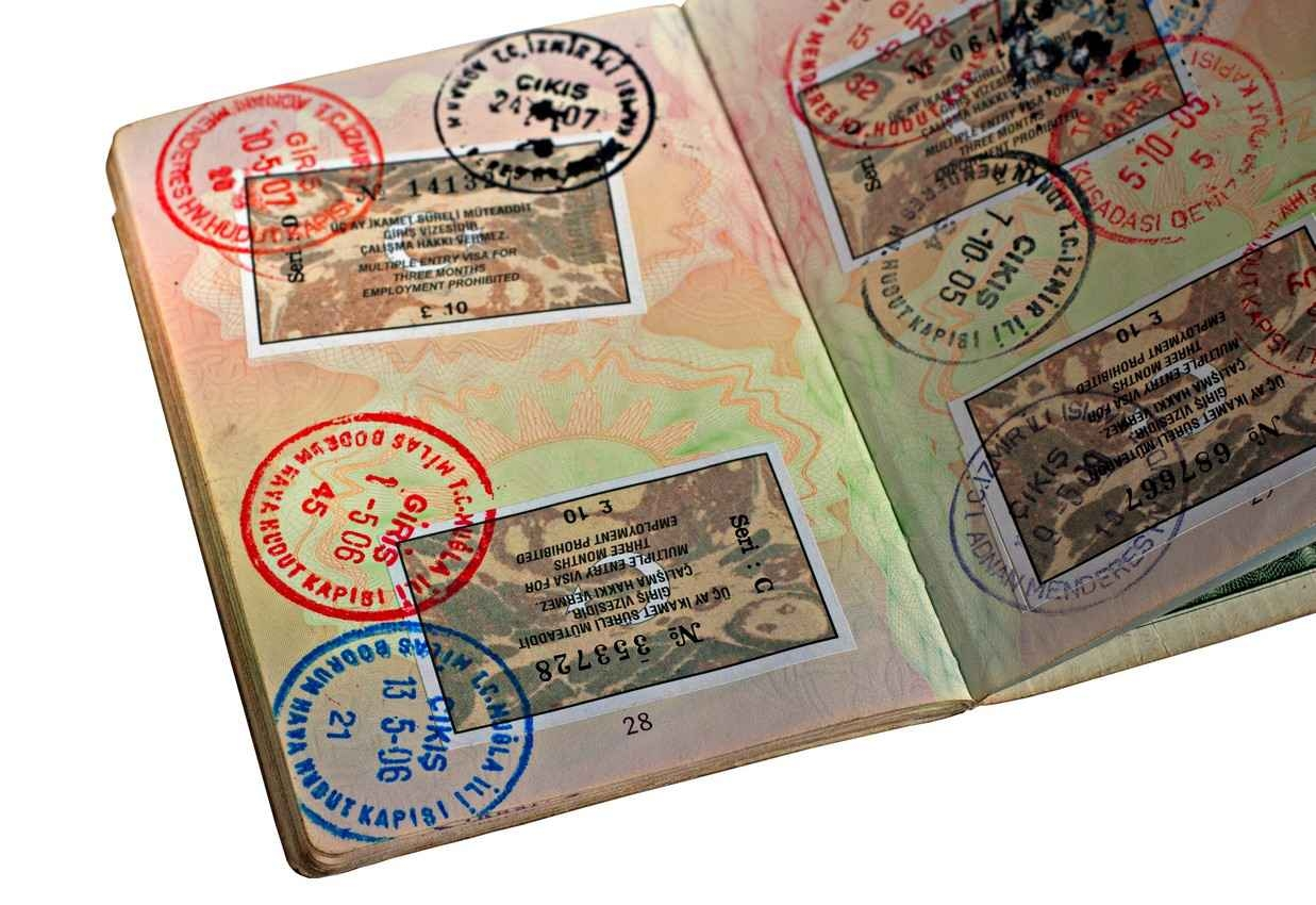 A passport book with lots and lots of stamps.