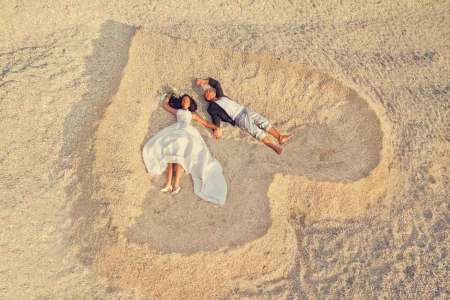 A man and a woman lying on the beach making a heart in the sand.