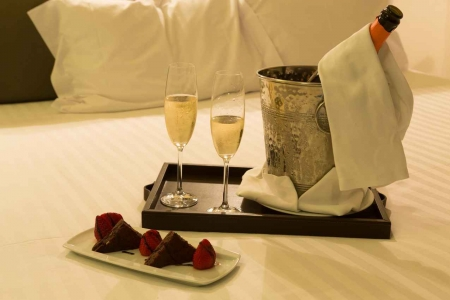 Two glasses of champagne near a chocolate and strawberry dessert on a bed in a Playa Del Carmen resort.