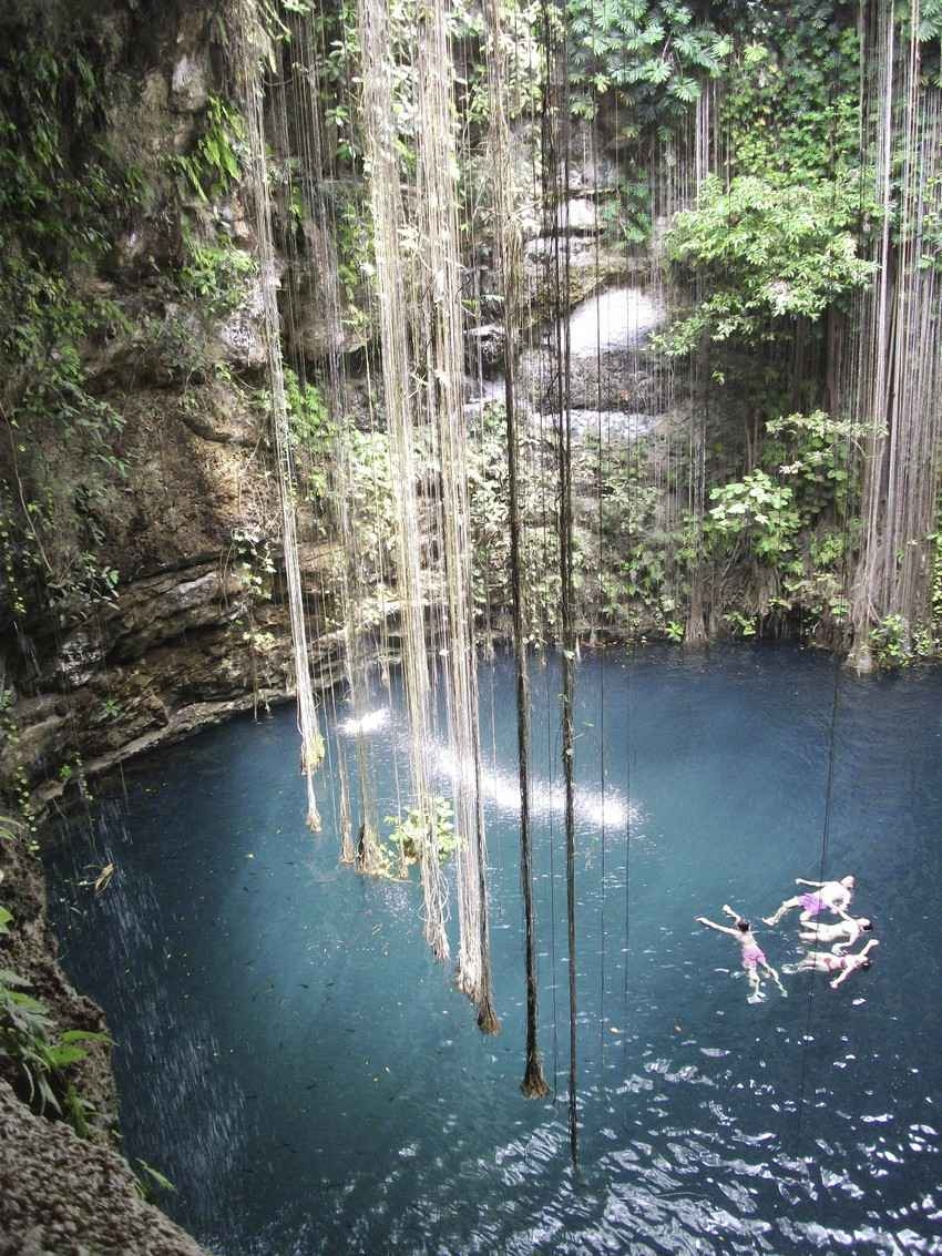 A group of people swimming and playing inside a cenote near Playa Del Carmen.