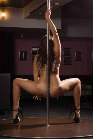 A dancer at an exotic club in Playa Del Carmen dancing spinning on a pole.