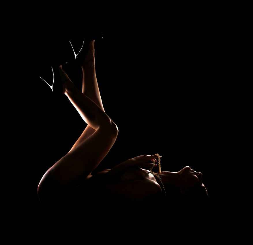 An exotic dancer lying on her back with her legs up in the air under extremely low lighting.