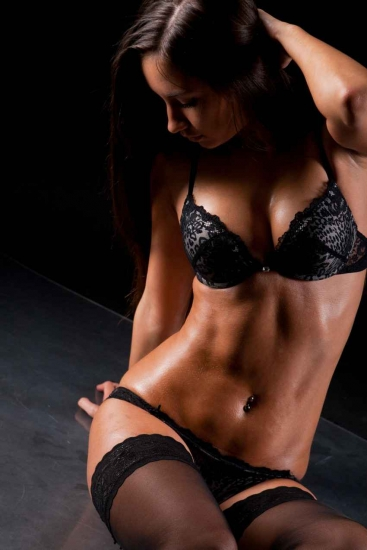 A sexy exotic dancer wearing black lingerie.