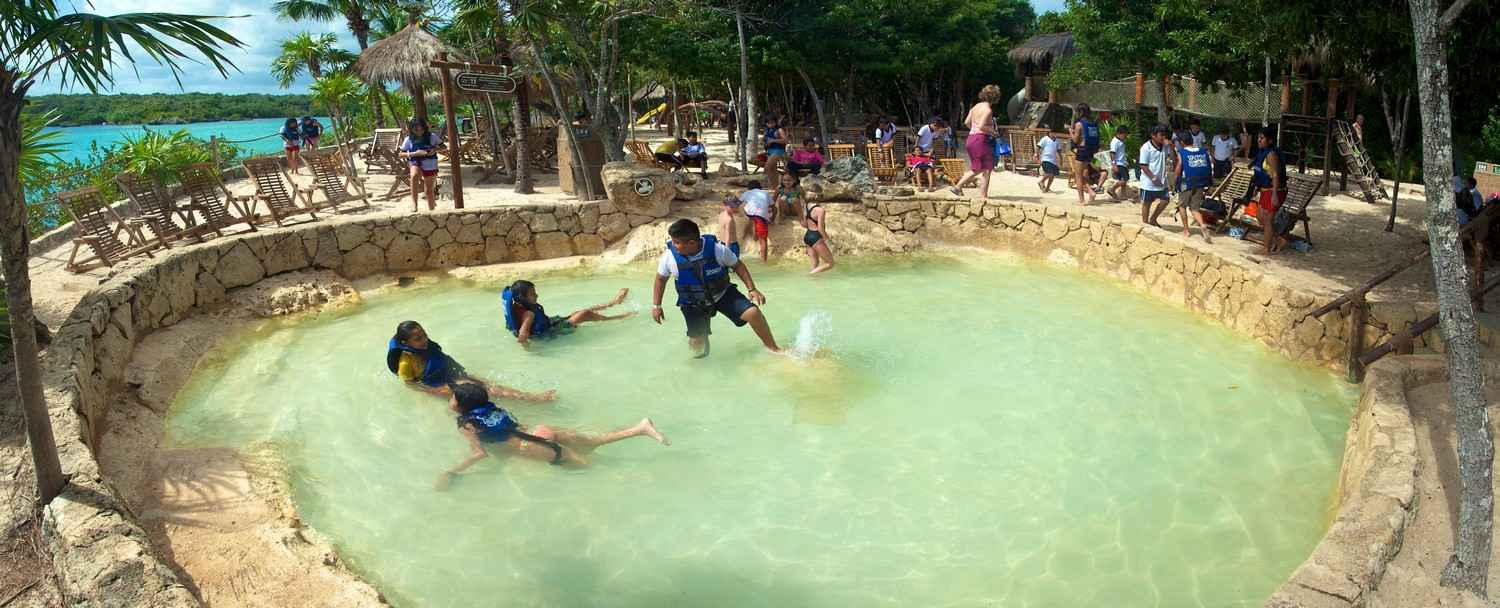 Several children with an instructor at the Xel-Ha themepark natural pool.