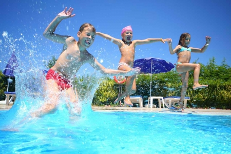 Three children jumping into a swimming pool.