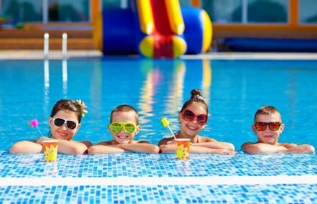Four children with sunglasses and drinks in a swimming pool.