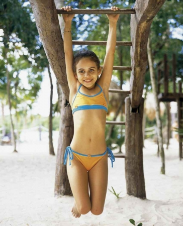 A young girl swinging from several monkey bars.