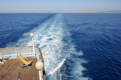 A lounge chair on a ferry boat in the sea.
