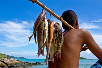 A man is holding a number of fish that he caught over his shoulder.