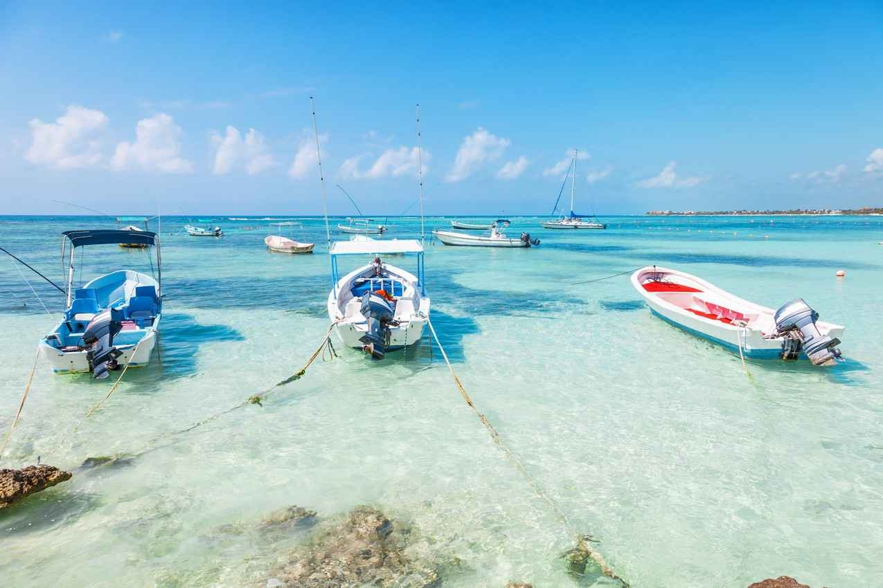 A group of several fishing boats anchored just off the shore in Playa Del Carmen.