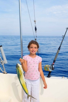 A young girl is holding up a fish that she caught.