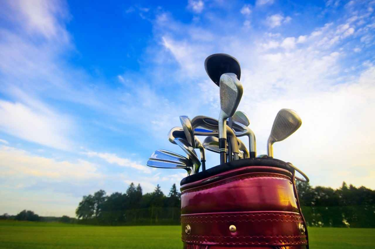 A set of golf clubs and a bag on a course.