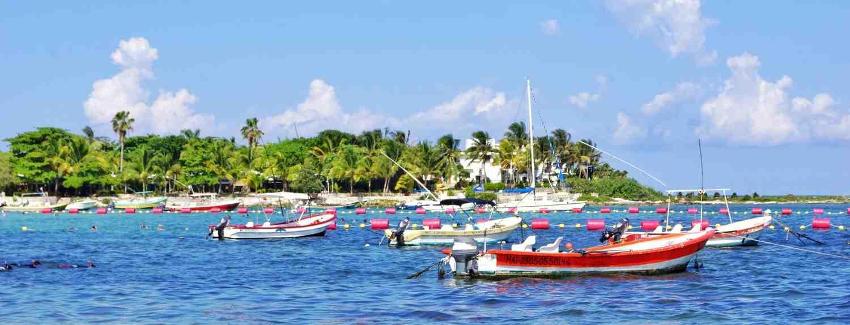 Several boats floating peacefully in Akumal bay near Playa Del Carmen.