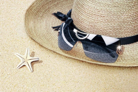 A sun hat with sunglasses on the sand.