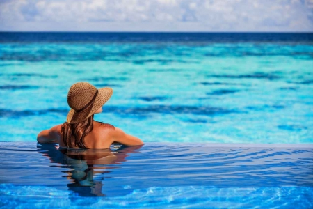A woman wearing a sun hat in an infinity pool overlooking the crystal clear blue water.