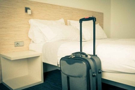 A suitcase waiting to be unpacked in a hotel room.