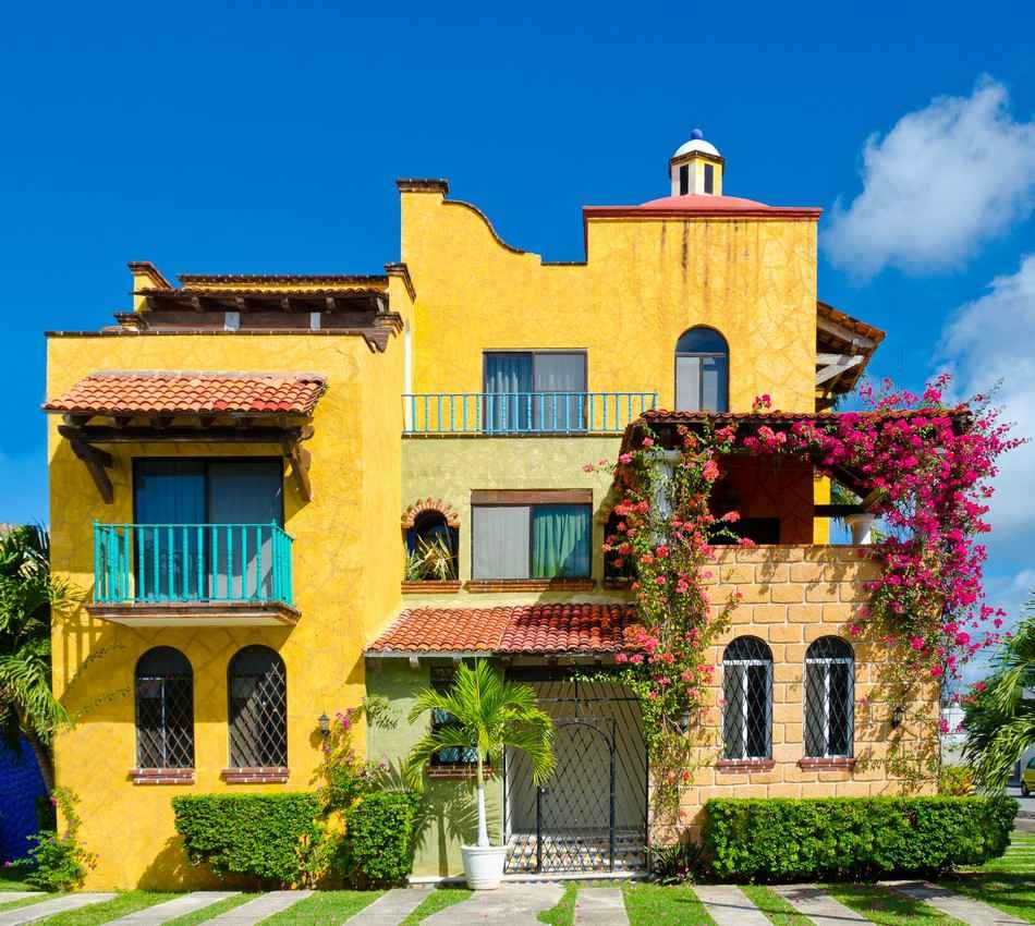 A beautiful yellow house in Playa Del Carmen that is surrounded by obviously well-kept plants.