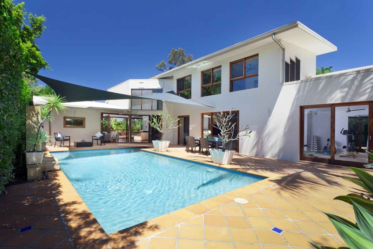 A beautiful villa with a large swimming pool in the back.