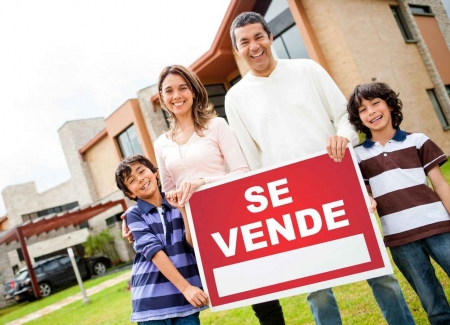 A family holding a for sale sign written in Spanish.