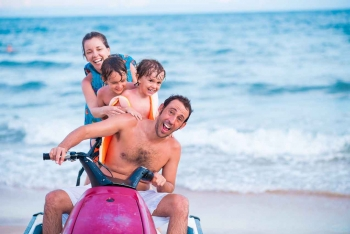 A family of four riding a single jet ski near the beach in Playa Del Carmen.