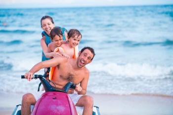 A family of four riding a single jet ski near the beach in Playa Del Carmen.