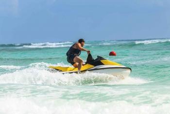 A man riding a jet ski near the beach.