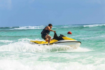 A man riding a jet ski near the beach.