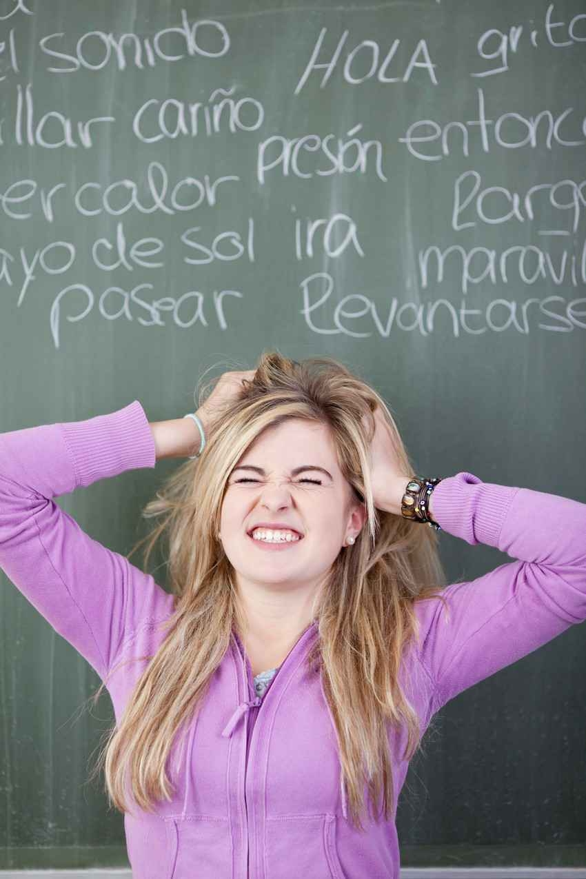 A woman pulling her hair out because she is frustrated while learning a foreign language.