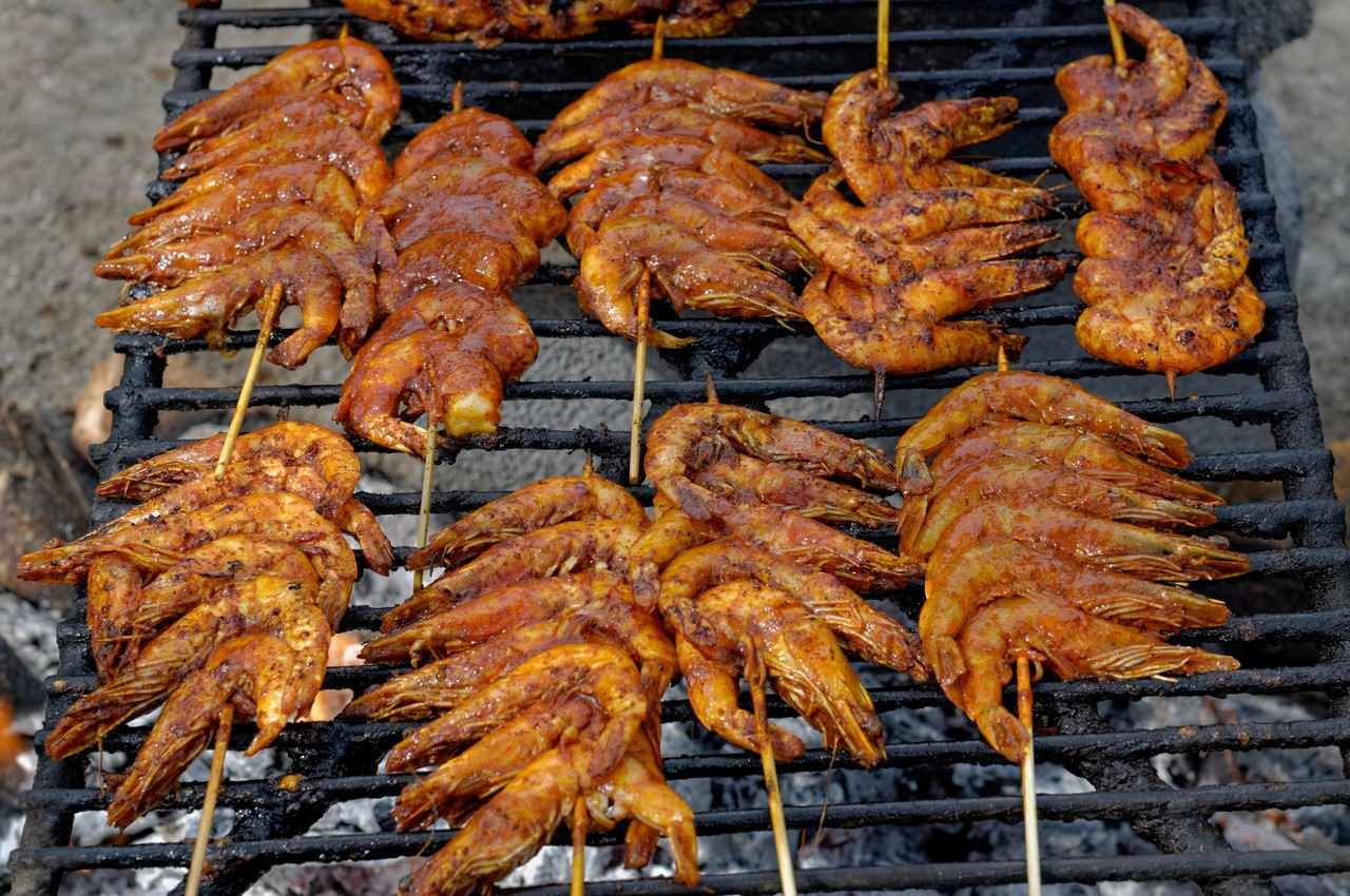 Heavily seasoned shrimp on skewers cooking over a charcoal grill.