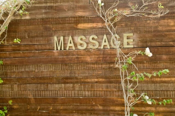 A sign on the wall of a spot that says massage.