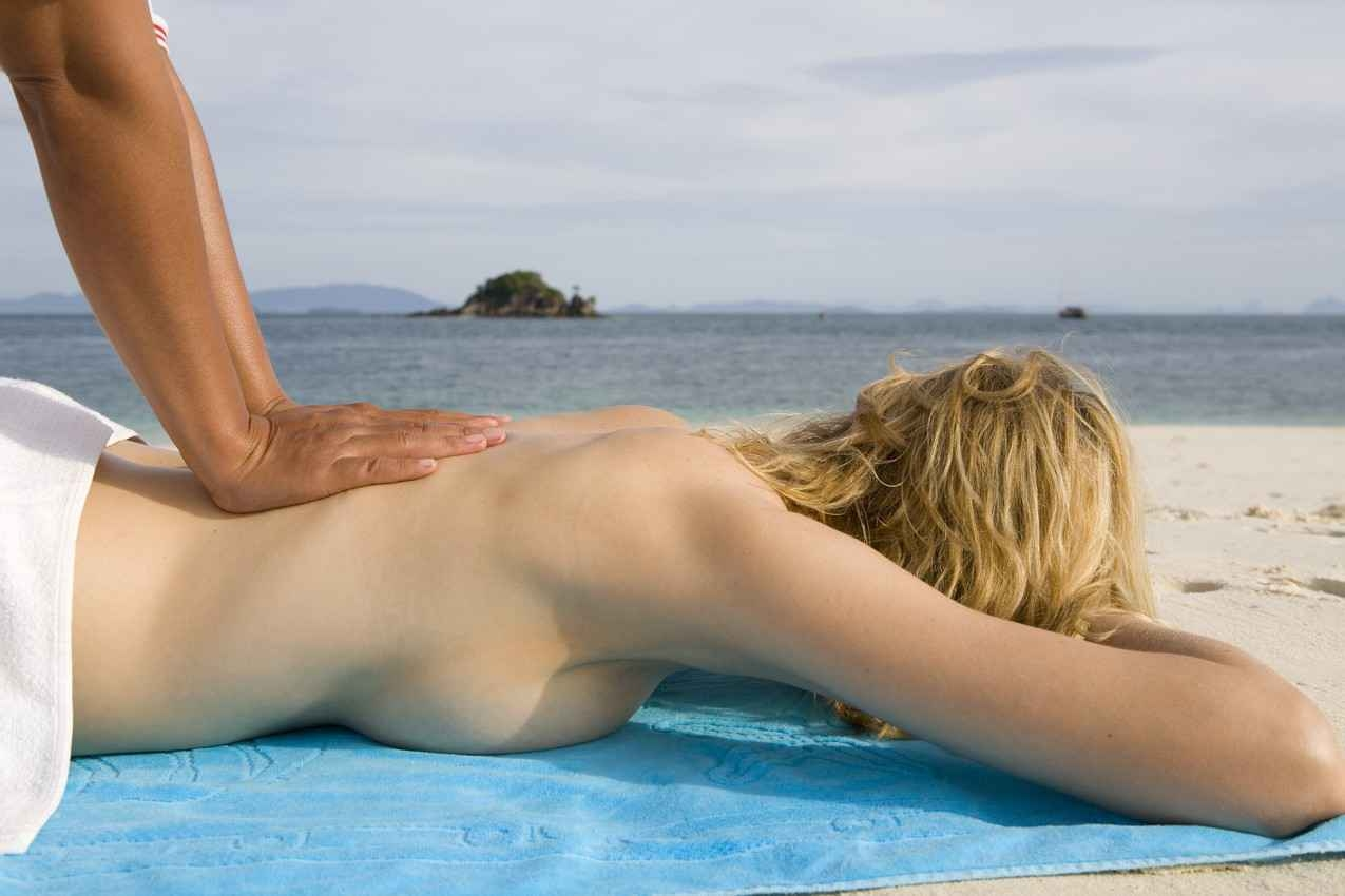 A topless woman receiving a massage on the beach.