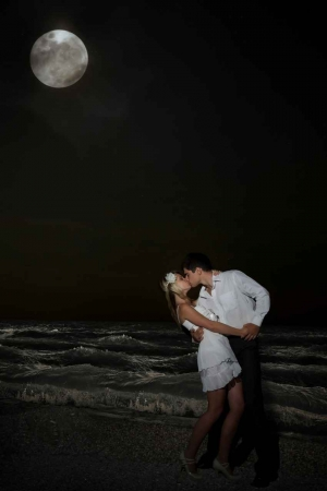 A man and a woman kissing on the beach with a full moon in the background.