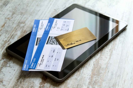 Economy class tickets, a mock credit card, and a tablet PC for searching for vacation packages on the Internet.