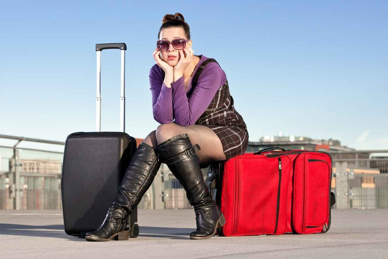 A woman sitting on a suitcase package with knee-high boots and a rolling suitcase.