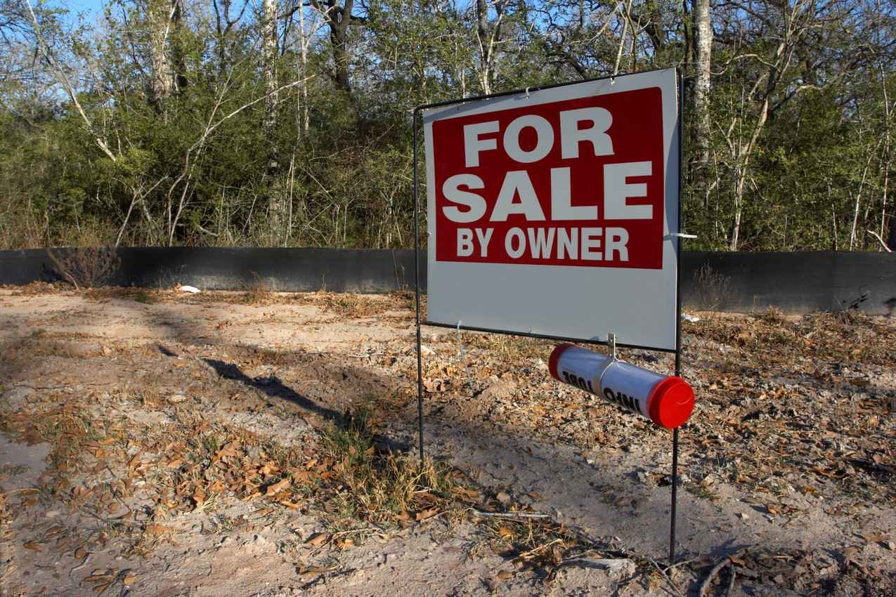 A FOR SALE BY OWNER property sign.