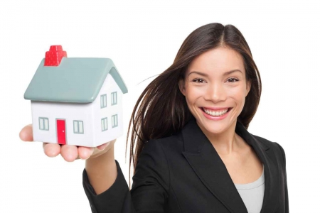 A friendly real estate agent holding up a plastic house.