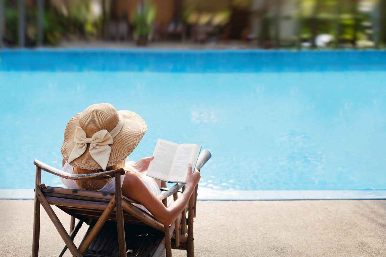 A woman in a bikini enjoying her backyard swimming pool.