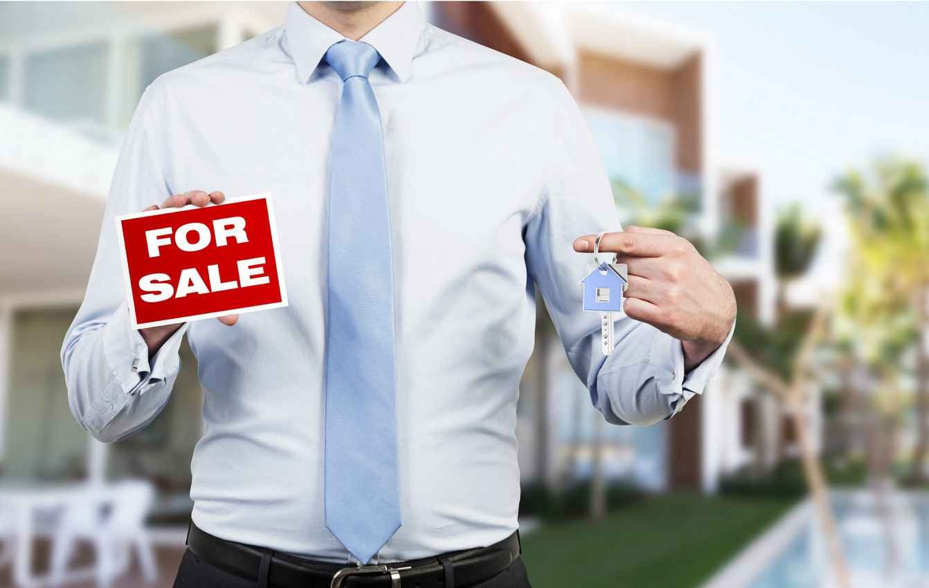 A realtor holding a for sale sign in one hand and a key in the other hand.