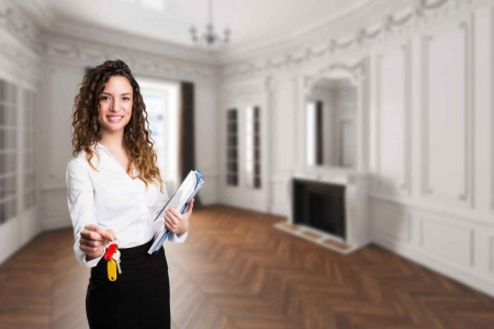 A realtor with long curly hair holding keys and several descriptive flyers.