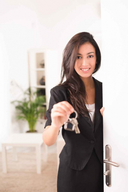 A sexy realtor holding several keys to a home.
