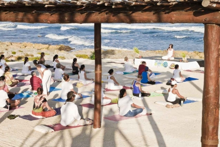 A large group of men and women doing yoga on the beach.