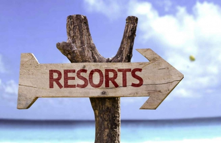 A resorts arrow sign on the beach.