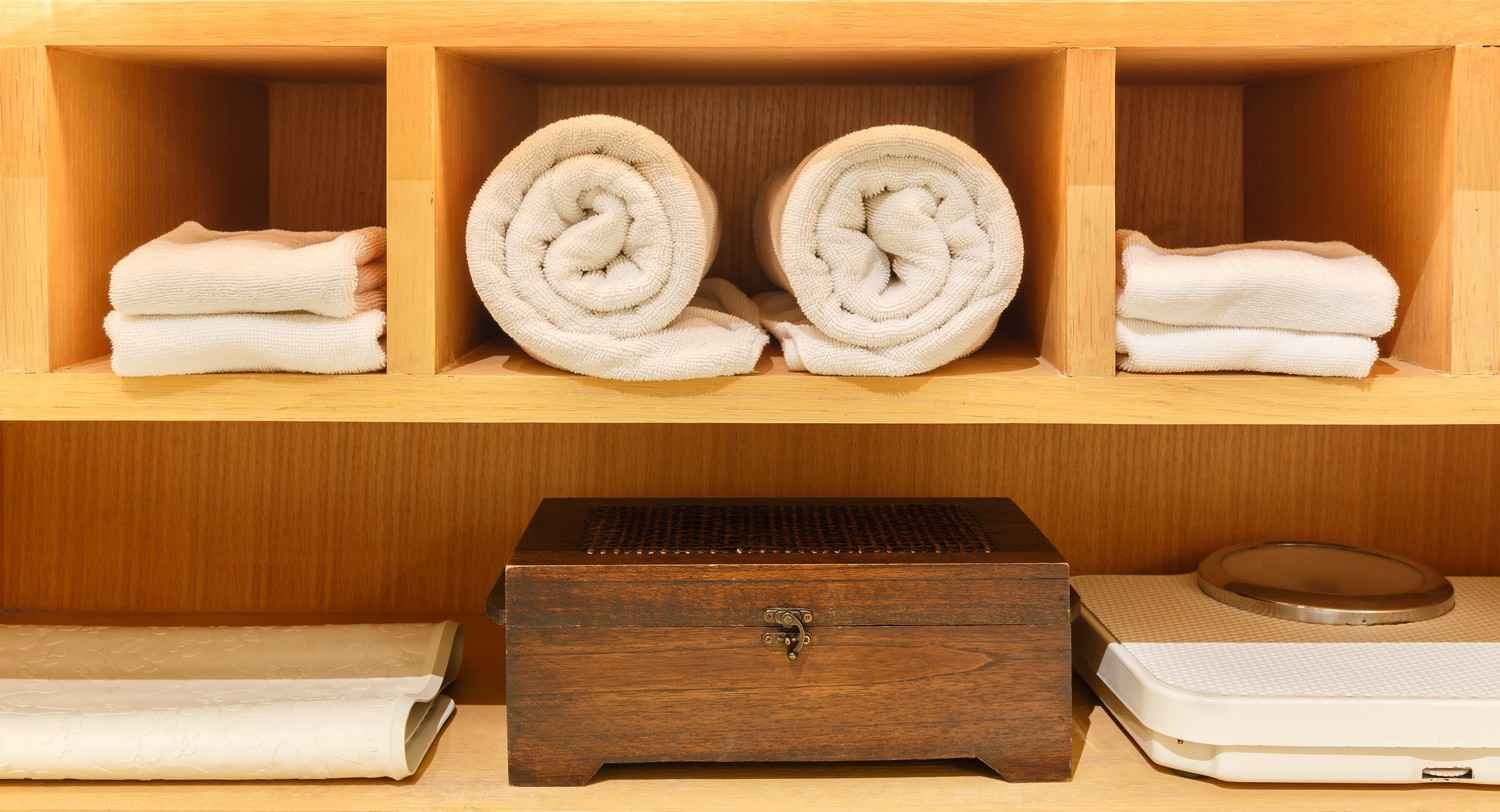 A closet in a resort that features large and small towels with a scale and a storage box.