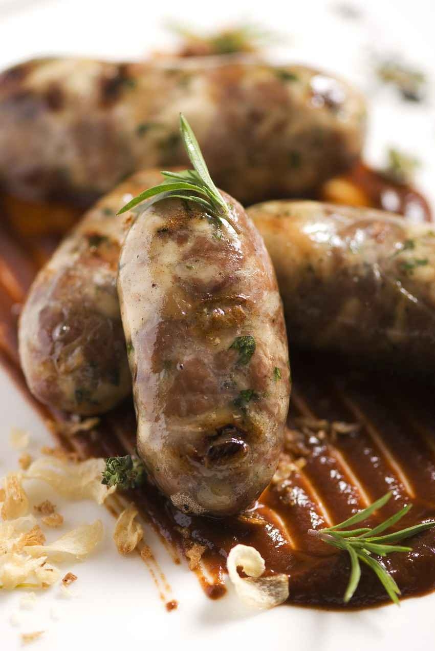 Several Italian sausages on a plate with gravy.