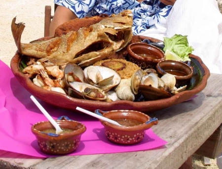 A large plate of various seafood with sauce on the side.